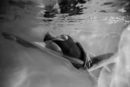 photo femme sous l'eau en piscine noir et blanc